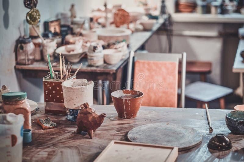黏土陶瓷工舒适工作场所有许多不同的工具的 库存图片