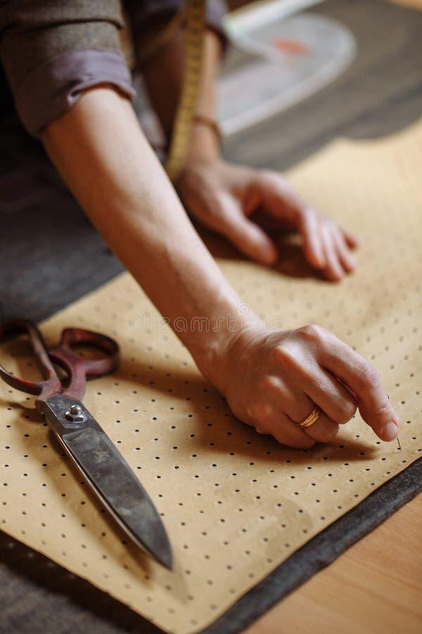 黏附别针的裁缝对布料样式在缝合的车间女性 免版税库存照片