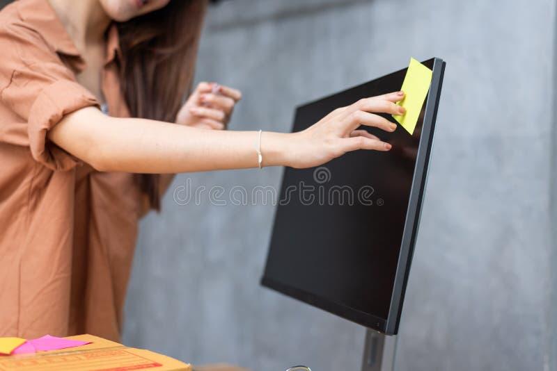 黏附命令名单备忘录的女商人在提醒的显示器能送小包到顾客 事务和服务 免版税图库摄影