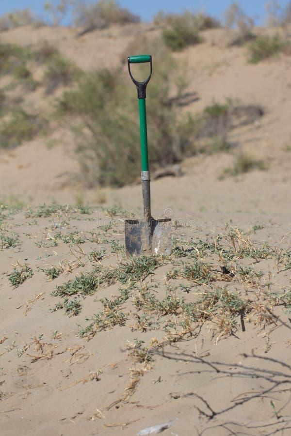 黏附在沙子的一把铁锹 库存照片