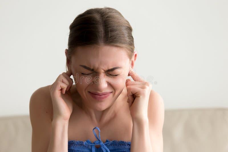 黏附在耳朵,不听的nois的年轻懊恼妇女手指 免版税图库摄影