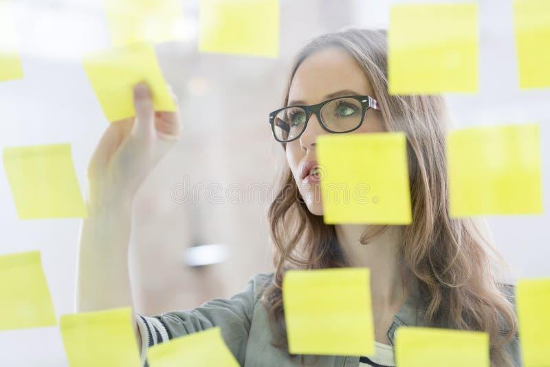 黏附笔记的年轻女实业家在玻璃墙 免版税库存照片