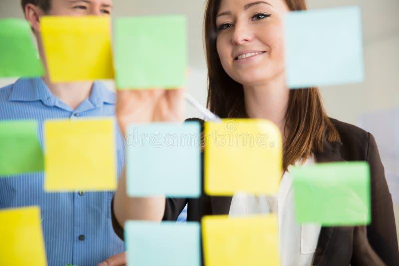 黏附笔记的微笑的女实业家在玻璃由同事 免版税库存照片
