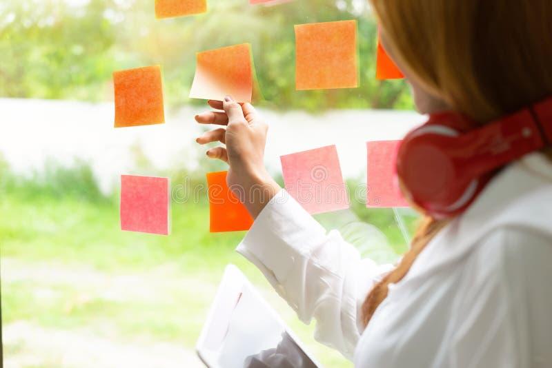 黏附黏着性笔记的妇女在玻璃墙在有葡萄酒口气的办公室 库存图片