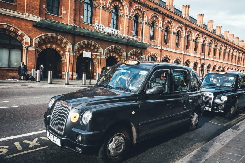 黑人出租汽车中止和等待乘客或旅客在Cross圣Pancras国王驻地前面 库存照片