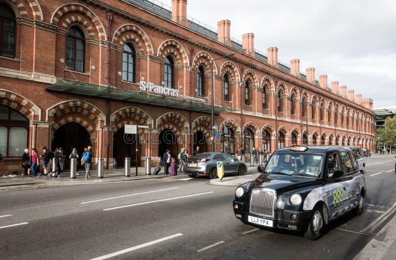 黑人出租汽车中止和等待乘客或旅客在Cross圣Pancras国王驻地前面 免版税库存图片