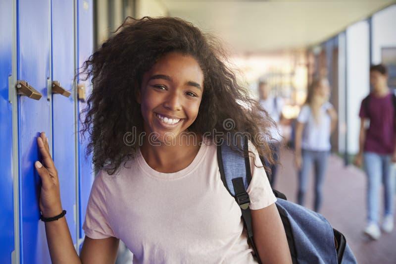 黑人十几岁的女孩画象由衣物柜的在学校走廊 免版税库存图片