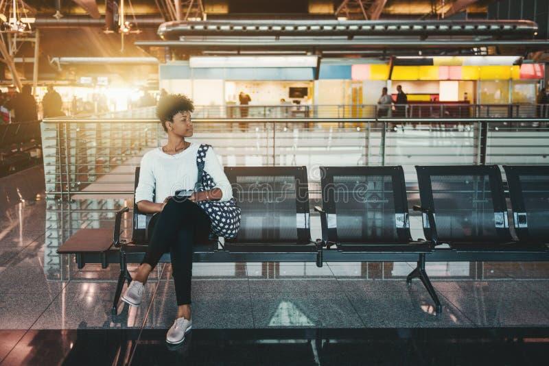 黑人女孩在机场终端等待她的飞机 免版税图库摄影