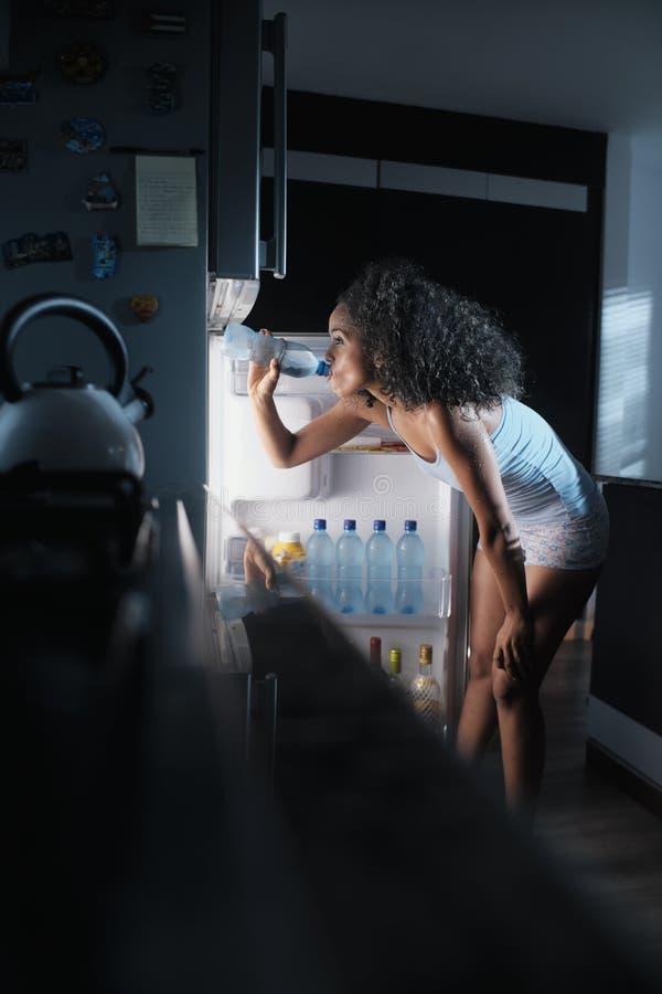 黑人妇女冒汗的和饮用水在晚上 图库摄影
