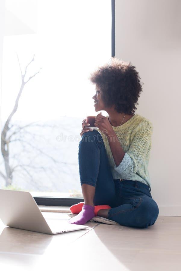 黑人妇女在地板上的客厅 库存图片