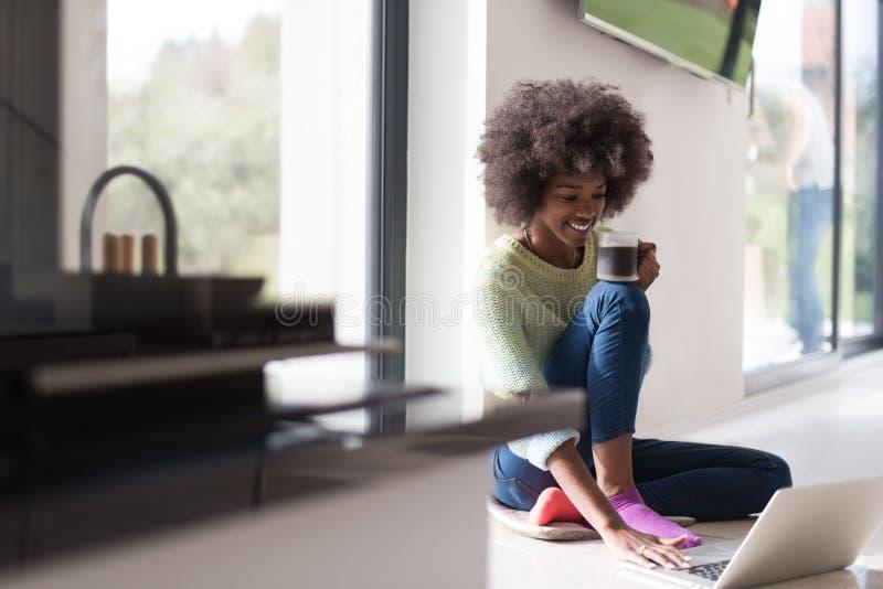 黑人妇女在地板上的客厅 库存照片