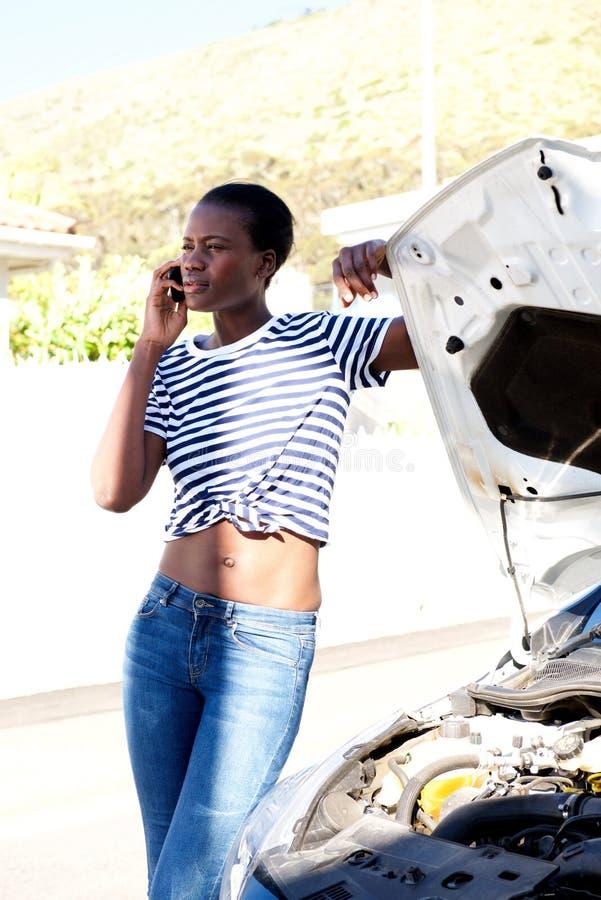 黑人妇女支持失败的汽车和要求在手机的协助 免版税库存照片