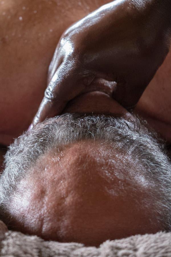 黑人妇女给脖子按摩一个年长白种人人 库存照片