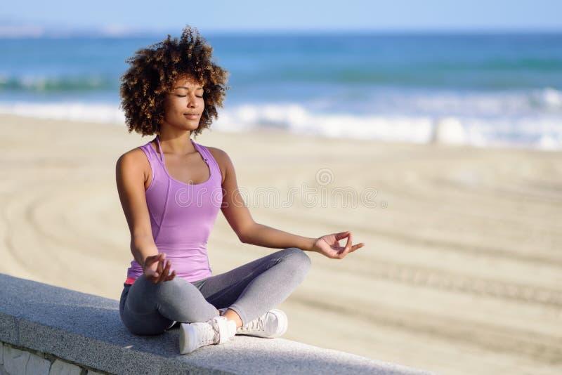 黑人妇女,非洲的发型,在与在海滩闭上的眼睛的莲花asana 免版税库存图片