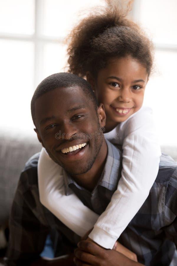 黑人拥抱父亲和小的女儿户内 库存图片
