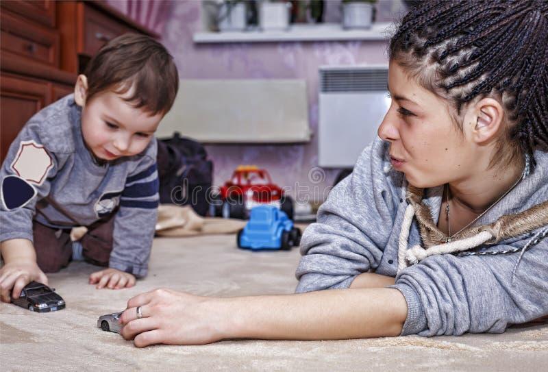 黑人母亲,小儿子,与汽车的戏剧,愉快的家庭,非立场 免版税库存图片