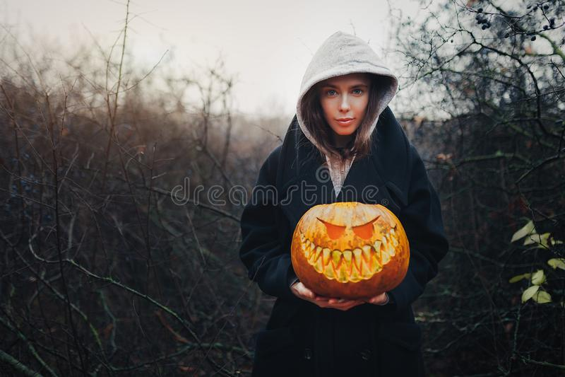 黑人现代生活方式巫婆愉快的万圣夜画象敞篷的和黑外套在木灌木森林背景覆盖 免版税图库摄影