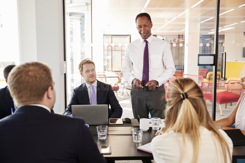 黑人男性经理对同事演讲在会议上微笑 免版税图库摄影