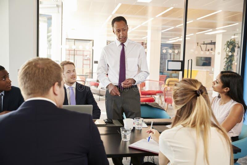 黑人男性经理对同事演讲在会议上 免版税库存照片