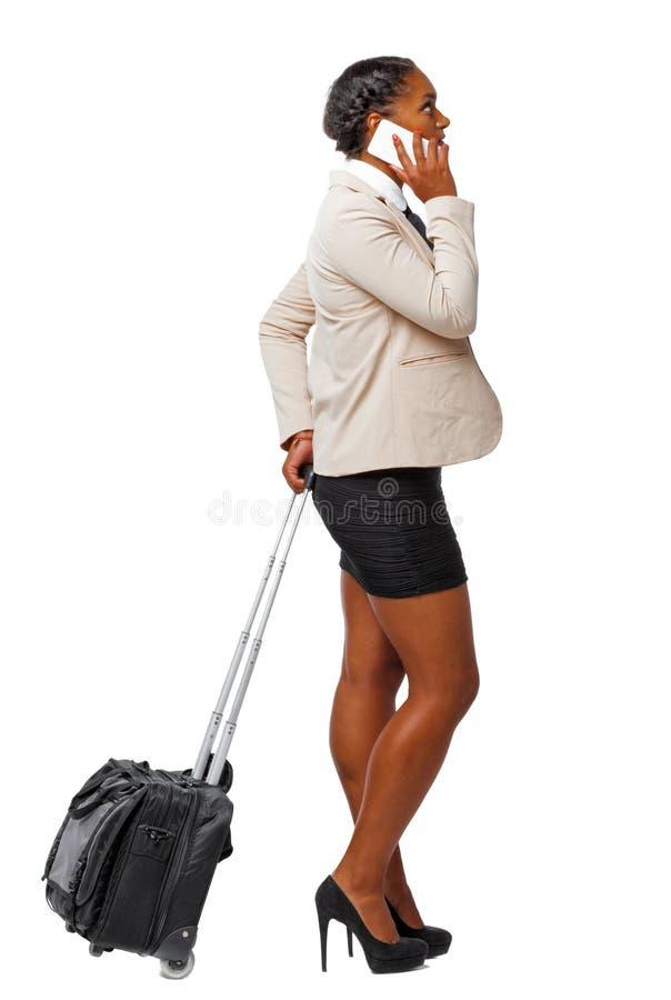 黑人非裔美国人的侧视图正式服装的带着有智能手机的一个手提箱 库存图片