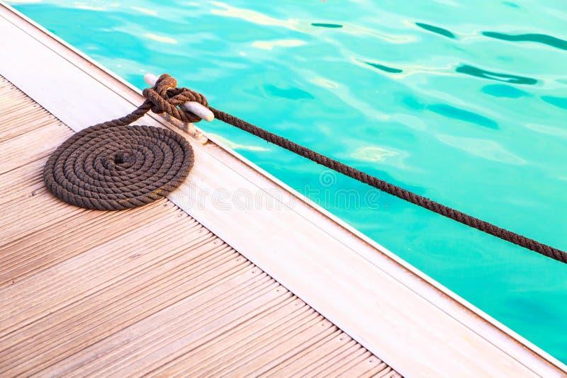 黑停泊绳索在木码头的圈子安排有蓝色wa的 库存照片