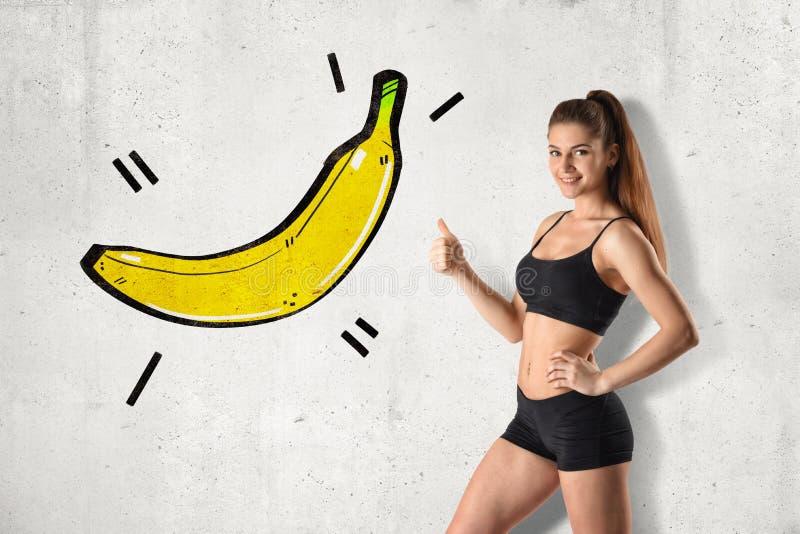 黑健身房庄稼上面和短裤的年轻适合的妇女站立在半轮做赞许指向大香蕉图画的  免版税库存图片