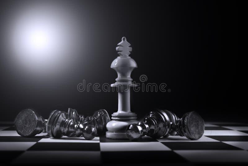 黑典当棋子由白色国王棋子击败了 库存图片