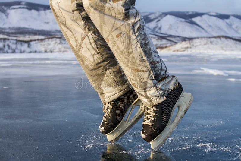 黑冰鞋的一个溜冰者人在冬天温暖的滑雪裤子在冬天显示在神圣的贝加尔湖的清楚的蓝色冰的月亮步行 免版税库存图片