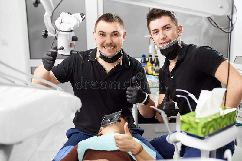 黑制服的两位男性牙医显示赞许并且微笑着对照相机 免版税库存照片