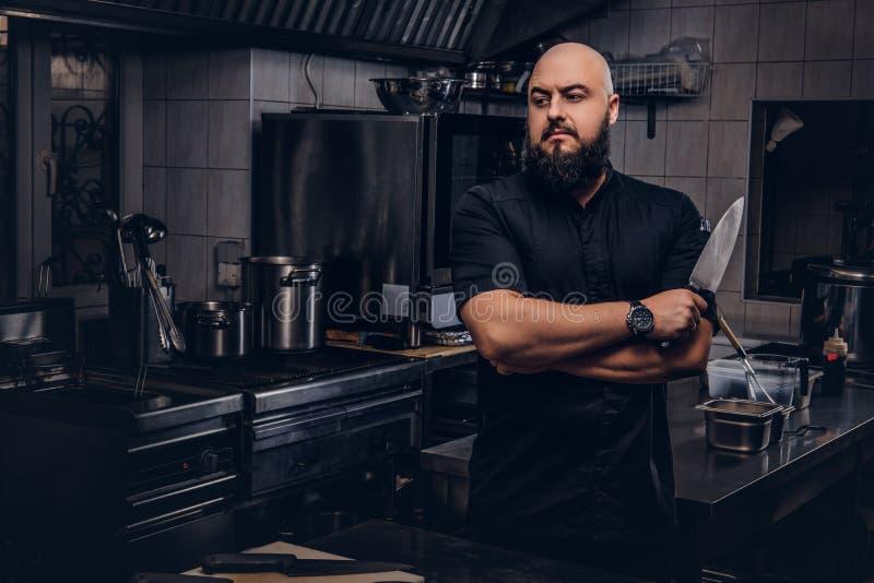 黑制服的有胡子的厨师在厨房里举行刀子和身分与横渡的胳膊 库存照片