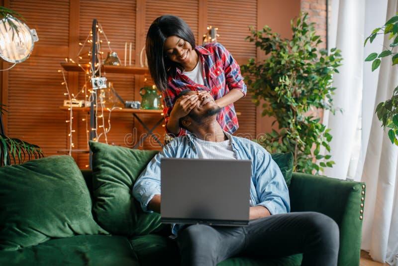 黑加上获得的膝上型计算机在沙发的乐趣 免版税库存图片