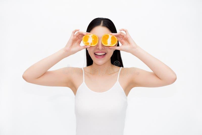 黑发的年轻亚裔美丽的微笑的妇女和白色在乐趣和幸福情感授予拿着柑橘桔子片断  免版税图库摄影