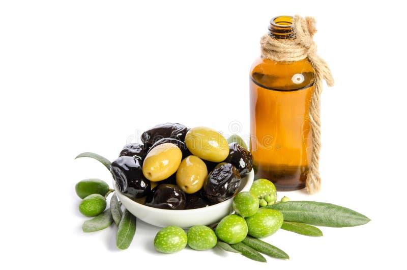 黑和绿橄榄在瓷碗和维尔京橄榄油混合了在一个水晶瓶在白色背景 库存图片