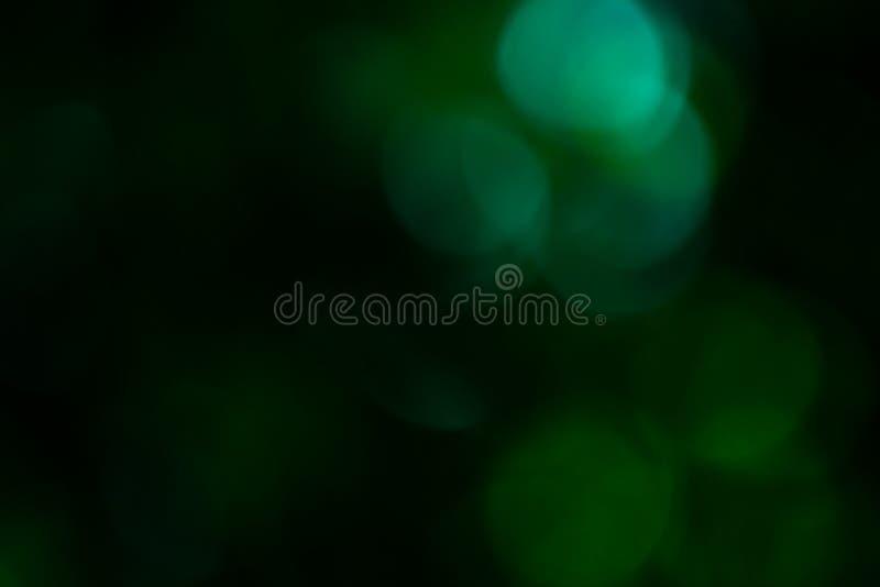 黑和绿色bokeh被弄脏在焦点,defocused抽象圆背景外面 库存图片