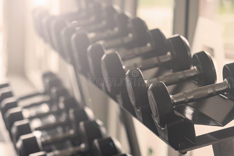 黑哑铃集合 结束在机架的许多金属哑铃在体育健身俱乐部,重量训练器材概念 免版税库存图片