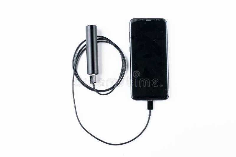 黑在白色背景隔绝的手机和充电器 r 免版税库存照片