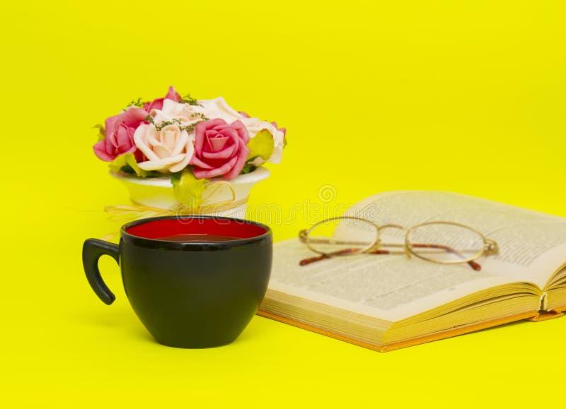 黑在黄色背景的杯子用热的茶和书 库存图片
