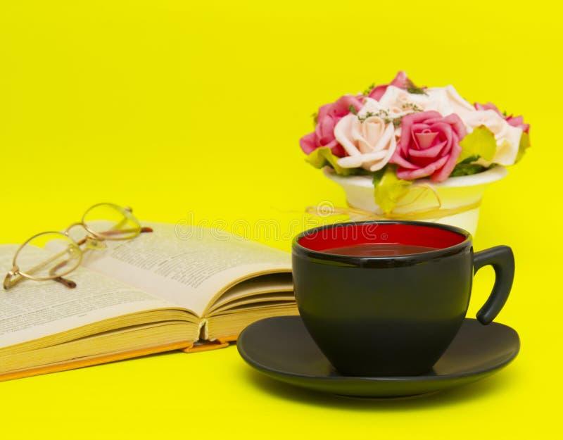 黑在黄色背景的杯子用热的茶和书 库存照片