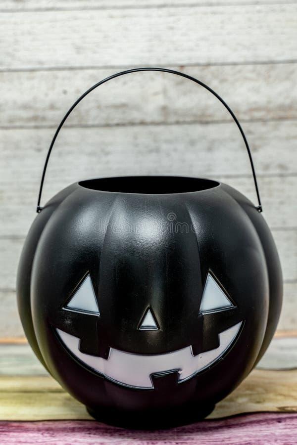 黑塑料南瓜把戏或款待桶,被隔绝 库存图片