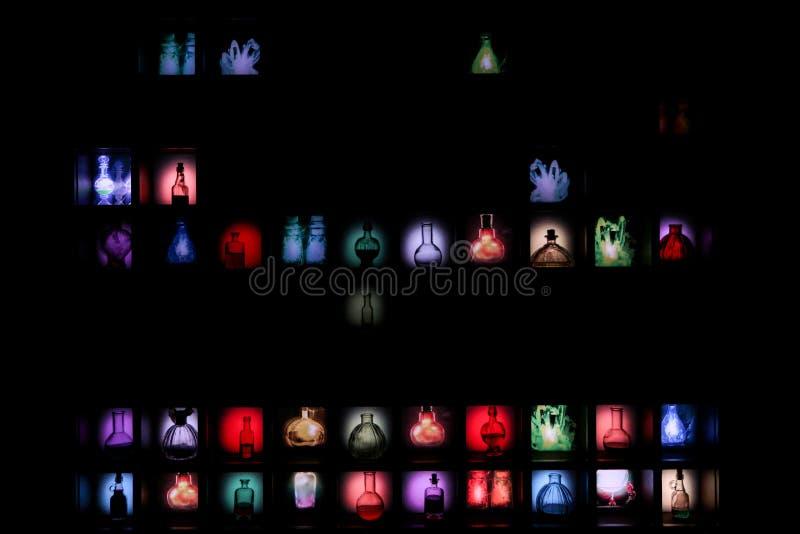 黑墙壁用各种各样的五颜六色的魔药 免版税库存照片