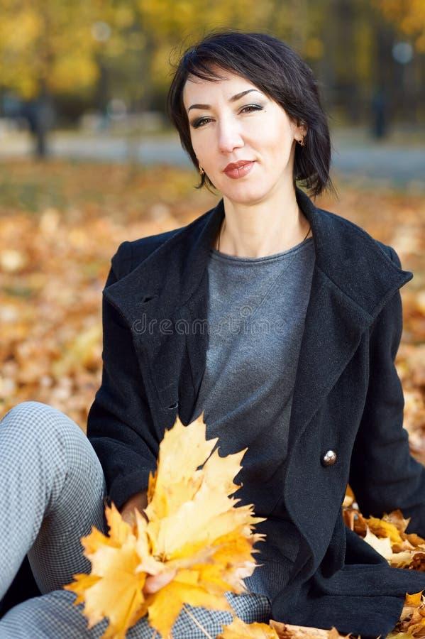 黑外套的女孩坐黄色在秋天城市公园,秋季离开 免版税库存图片