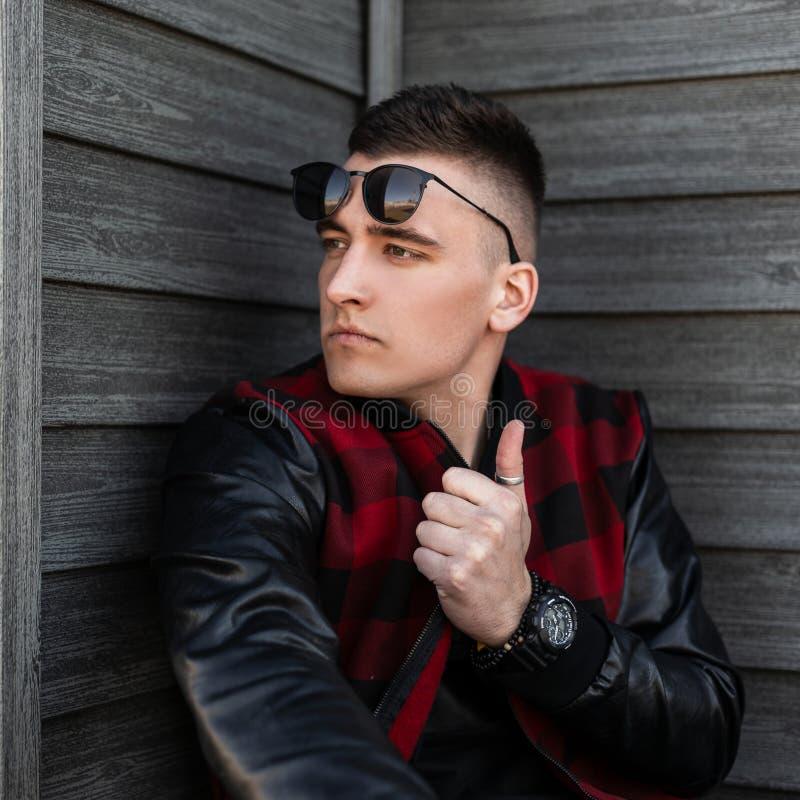 黑太阳镜的都市年轻行家人在有皮革袖子的一件时髦红色方格的夹克有一种时兴的发型的 免版税库存图片