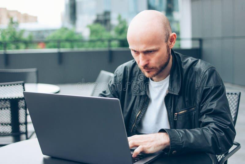 黑夹克的可爱的成人成功的秃头有胡子的人有在街道咖啡馆的膝上型计算机的在城市 免版税图库摄影