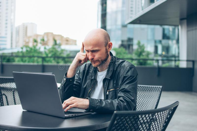 黑夹克的想法的可爱的成人成功的秃头有胡子的人有在街道咖啡馆的膝上型计算机的在城市 免版税库存照片