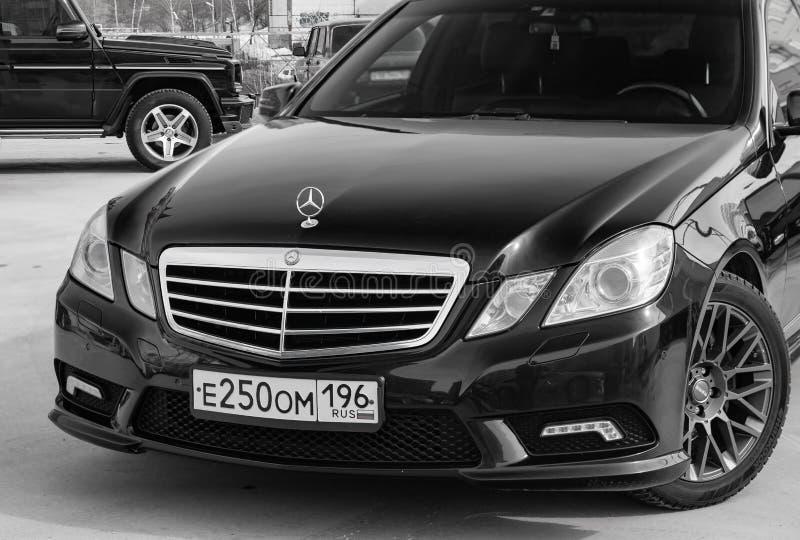 黑奔驰车E班的E250 2010与深灰内部的年正面图在一停车空间的优秀情况与灰色 免版税库存照片