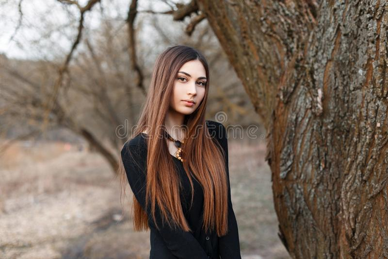 黑女衬衫的美丽的女孩在公园背景 及早 免版税库存图片