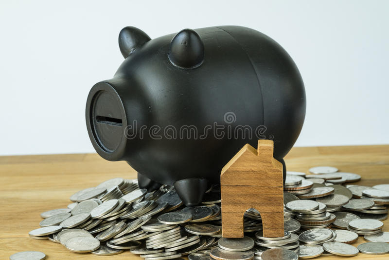 黑存钱罐和木微型房子堆的硬币  免版税图库摄影