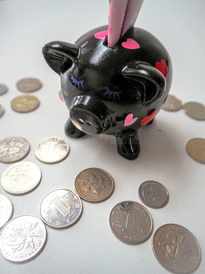 黑存钱罐用中国100张rmb钞票填装了并且驱散了在白色木背景的中国和香港硬币 免版税库存图片