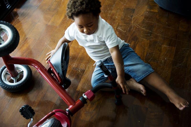 黑孩子跌下自行车 库存图片
