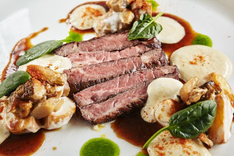 黑安格斯牛肉内圆角餐馆板材用在乳酪调味料和蘑菇Espuma的温暖的土豆 免版税库存图片